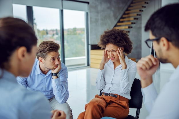 Femme d'affaires bouleversée assis en cercle avec un groupe de soutien et parler de problèmes
