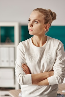 Femme d'affaires avec les bras croisés en regardant par la fenêtre