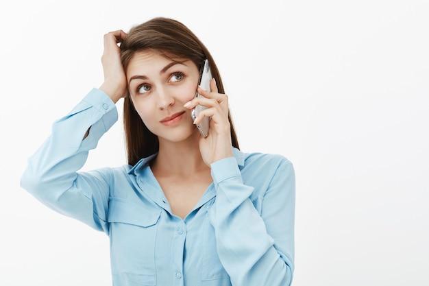Femme d'affaires brune confuse posant dans le studio