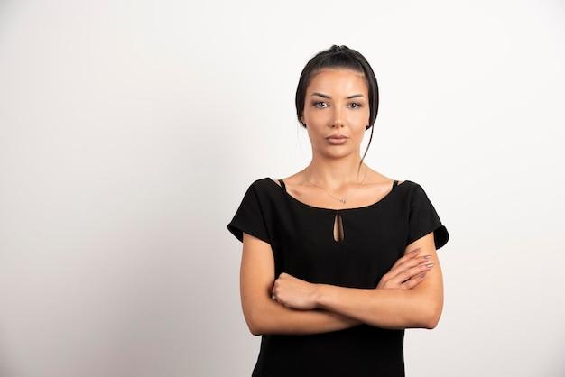 Femme d'affaires brune debout sur un mur blanc.