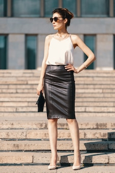 Femme d'affaires brune à la mode en jupe crayon en cuir
