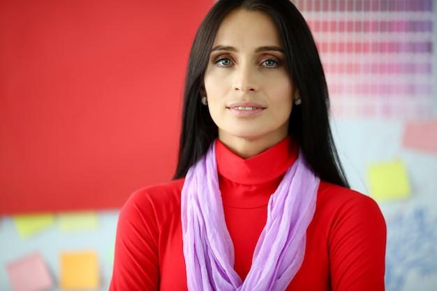 Femme d'affaires brune sérieuse en robe rouge portrait.