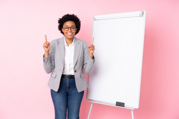 Femme d'affaires brune avec tableau blanc sur fond rose isolé