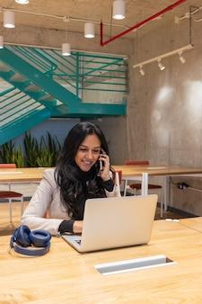 Femme d'affaires brune travaillant depuis son espace de travail