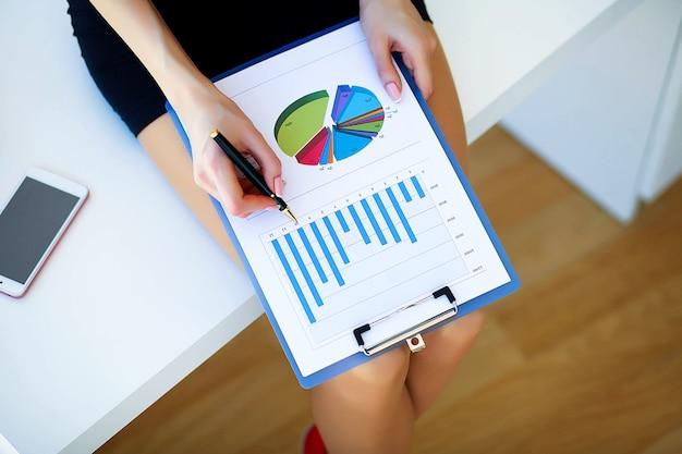 Femme d'affaires de bureau sourit et tenant le dossier avec des diagrammes. w
