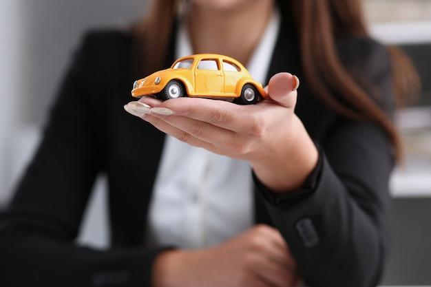 Femme affaires, bureau, tient, miniature, jouet, jaune, voiture