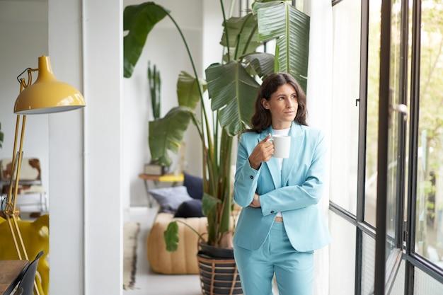Femme d'affaires buvant du café se penchant hors de la fenêtre du bureau, femme inspirée à la recherche pensive et r...