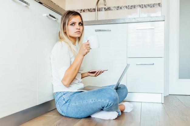 Femme d'affaires buvant une tasse de café et utilisant son ordinateur portable pour travailler par beau matin.