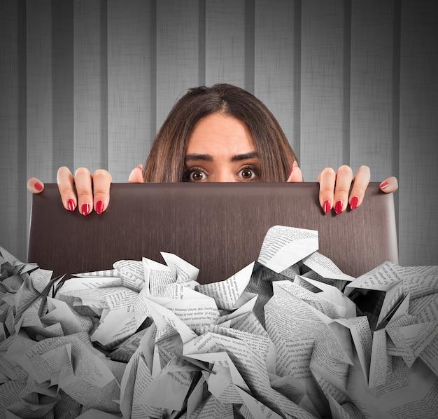 Femme d'affaires cachée derrière l'écran du portable submergé par les draps