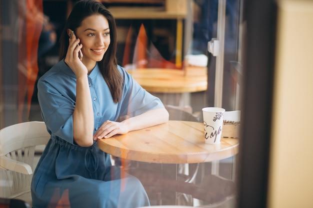 Femme d'affaires avec café et parler au téléphone dans un café