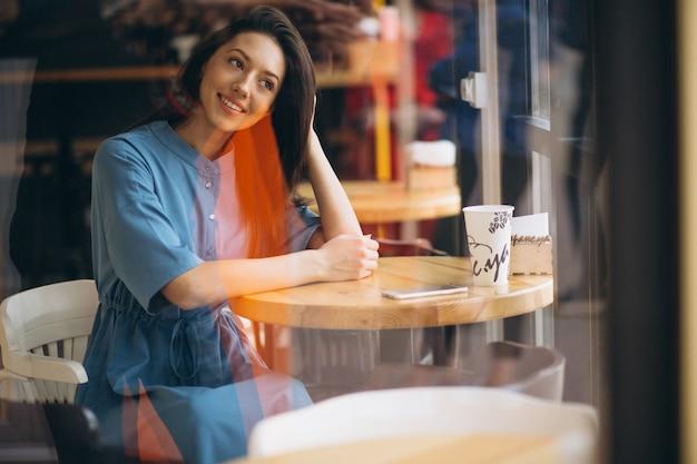 Femme d'affaires avec café et téléphone dans un café