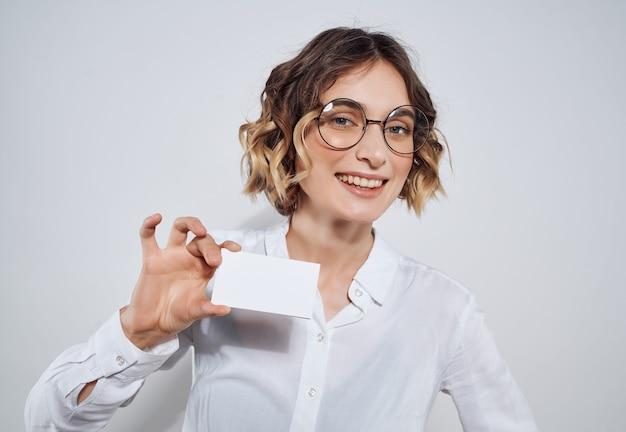Femme d'affaires avec carte de visite en mains documents publicité studio