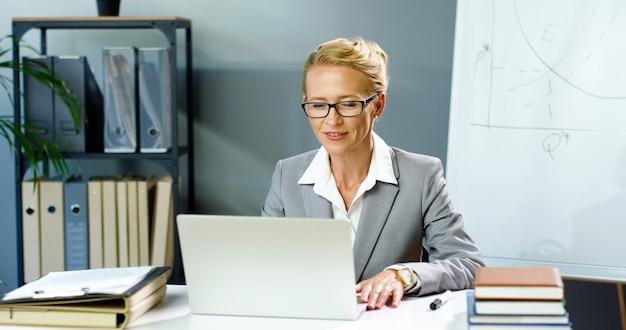 Femme d'affaires caucasienne dans des verres assis au bureau et parler via webcam sur ordinateur portable, vidéochat et éducation des entreprises. entraîneur féminin enregistrement vidéo blog blogger vidéochat en ligne sur ordinateur.