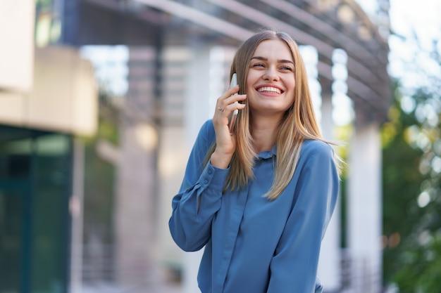 Femme d'affaires caucasienne parlant par téléphone tenant du café pour aller. une femme européenne réussie, parler au téléphone, debout sur un immeuble de bureaux moderne