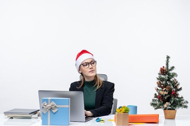 Femme d'affaires avec un chapeau de père noël assis à une table avec un arbre de noël et un cadeau