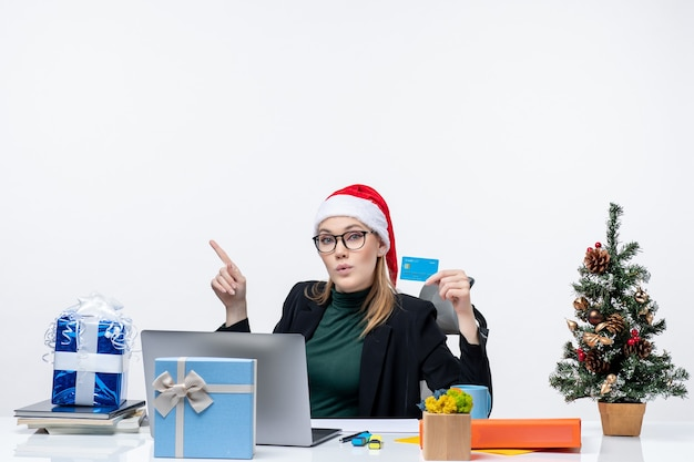 Femme d'affaires avec chapeau de père noël et portant des lunettes assis à une table tenant un cadeau de noël et une carte bancaire au bureau