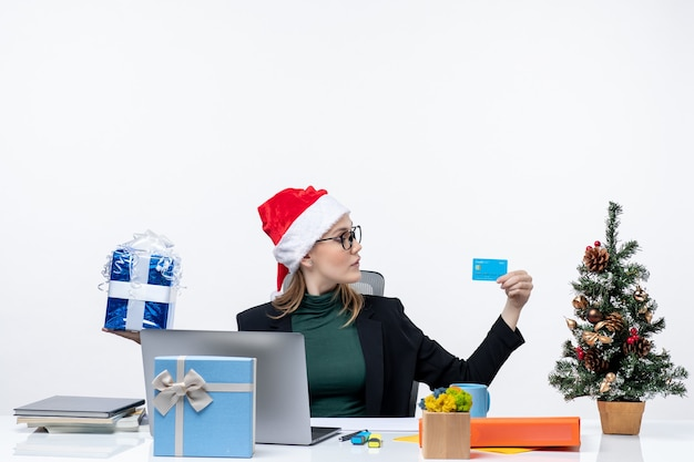 Femme d'affaires avec chapeau de père noël et portant des lunettes assis à une table tenant un cadeau de noël et une carte bancaire