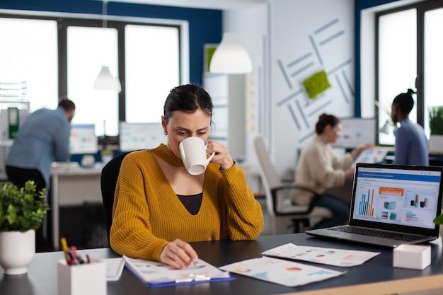 Femme d'affaires de chef de marque buvant une tasse de café analysant des graphiques financiers de démarrage