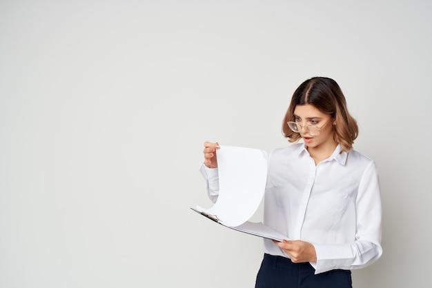 Femme d'affaires en chemise blanche documents travail fond clair