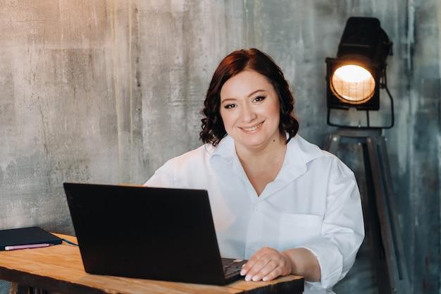 Une femme d'affaires en chemise blanche est assise à un bureau et travaille sur un ordinateur portable à l'intérieur.