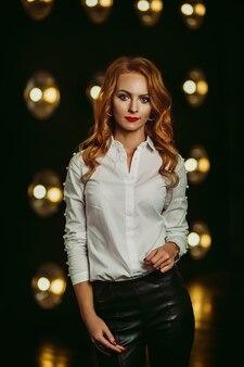 Femme d'affaires en chemise blanche sur fond de lampes allumées à l'intérieur d'un studio sombre. modèle aux cheveux longs et rouge à lèvres