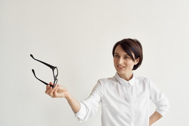 Femme d'affaires en chemise blanche et lunettes entre les mains d'un professionnel