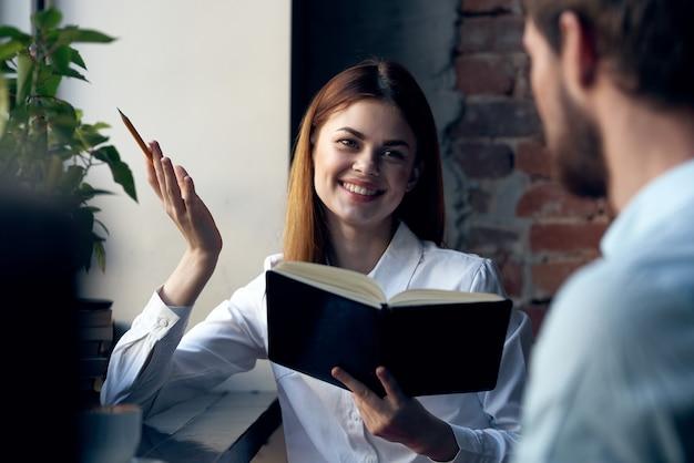 Femme d'affaires en chemise avec livre dans les mains à côté de l'homme