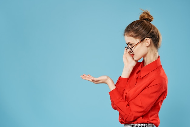 Femme d'affaires chemise rouge style élégant secrétaire travail émotions fond bleu. photo de haute qualité