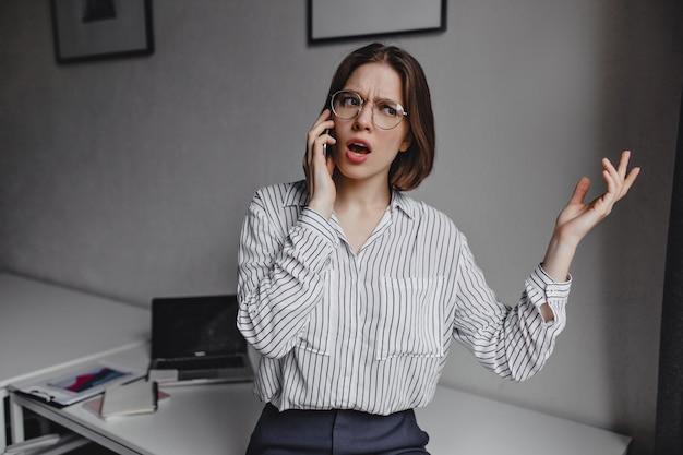 Femme d'affaires en chemisier élégant, parler émotionnellement au téléphone. plan d'une fille avec des lunettes sur fond de tableau blanc avec de la papeterie.