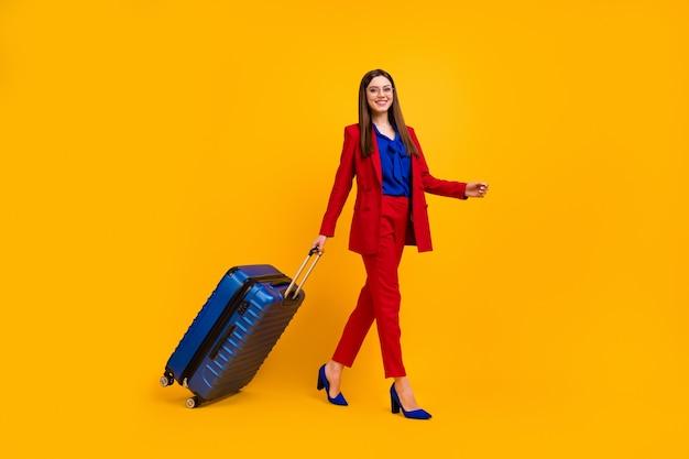 Femme d'affaires chic à pied roulant grosse valise