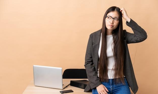 Femme d'affaires chinoise dans son lieu de travail ayant des doutes tout en se grattant la tête