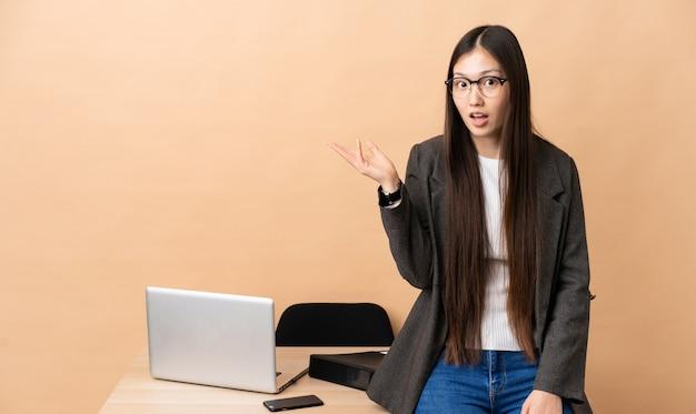 Femme d'affaires chinoise dans son lieu de travail faisant des doutes geste