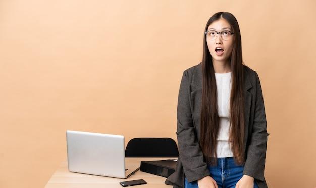 Femme d'affaires chinoise dans son lieu de travail en levant et avec une expression de surprise