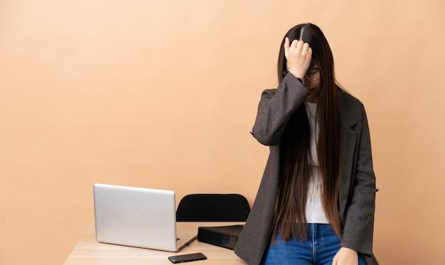 Femme d'affaires chinoise dans son lieu de travail avec maux de tête