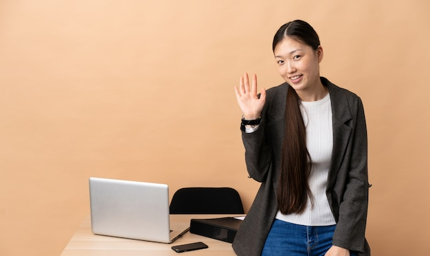 Femme d'affaires chinoise dans son lieu de travail saluant avec la main avec une expression heureuse