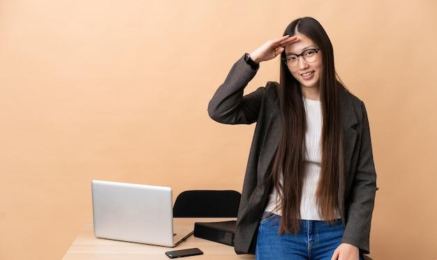 Femme d'affaires chinoise dans son lieu de travail, saluant avec la main avec une expression heureuse