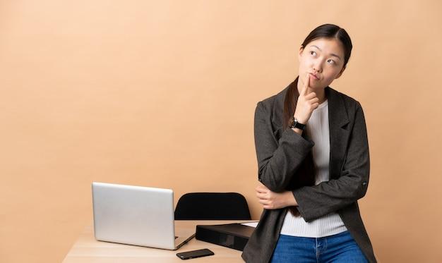 Femme d'affaires chinoise sur son lieu de travail ayant des doutes en levant les yeux
