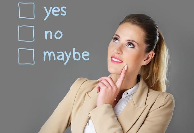 Femme d'affaires choisissant entre oui et non sur fond gris