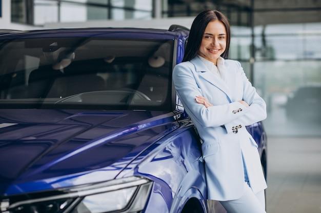 Femme d'affaires choisissant une nouvelle voiture dans une salle d'exposition de voiture
