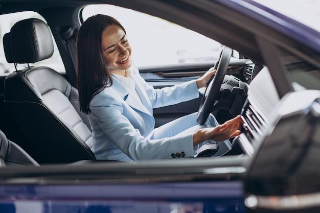 Femme d'affaires choisissant une voiture dans une salle d'exposition de voiture