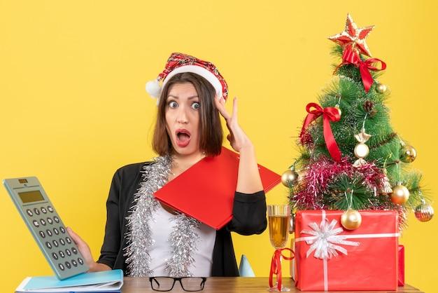 Femme d'affaires choquée en costume avec chapeau de père noël et décorations de nouvel an tenant calculatrice et assis à une table avec un arbre de noël dessus dans le bureau