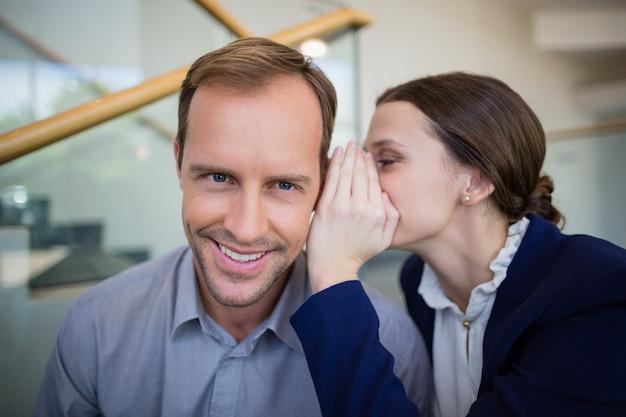 Femme d'affaires chuchotant quelque chose à son collègue
