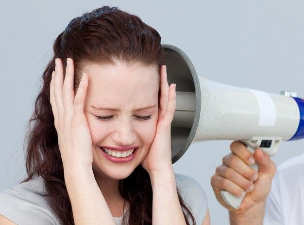 Femme d'affaires en colère à l'écoute d'un mégaphone