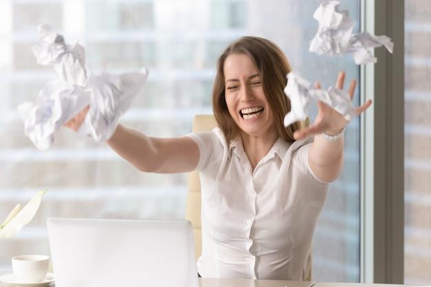 Femme d'affaires en colère jetant des papiers émiettés