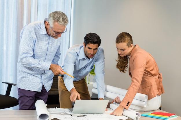 Femme affaires, collègues, discuter, plan, utilisation, ordinateur portable
