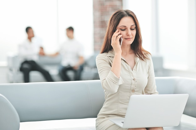 Femme d'affaires communique avec ses partenaires à l'aide d'un ordinateur portable et d'un smartphone
