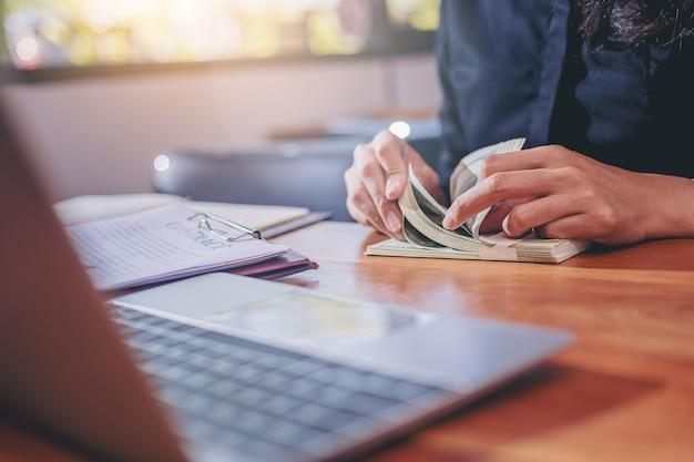 Femme d'affaires comptant de l'argent en dollars pour traiter et conclure un contrat en réunion de travail.