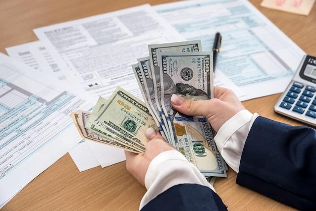 Femme d'affaires compte des dollars, sur le formulaire fiscal 1040