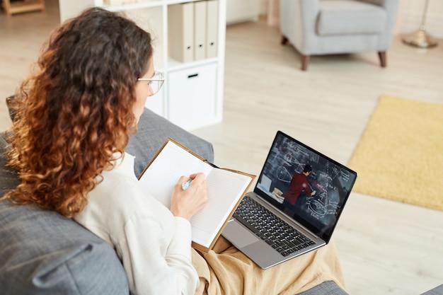Femme d'affaires concentrée assis sur le canapé à prendre des notes dans un ordinateur portable tout en regardant une vidéoconférence
