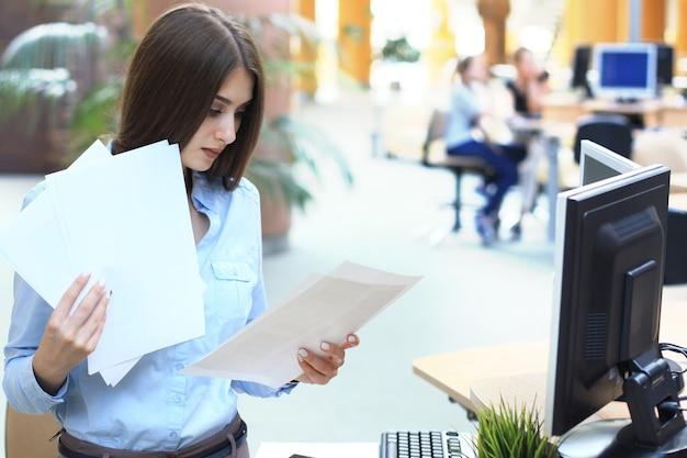 Femme d'affaires concentrée comparant des documents au bureau.
